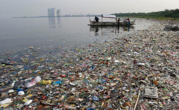 Fishermen work amidst floating garbage in Manila Bay. Photograph: Erik de Castro/Reuters