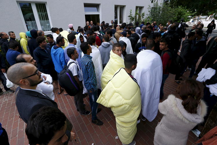 Migrants queue at a registration office at the overcrowded Friedland refugee camp. Credit: Reuters