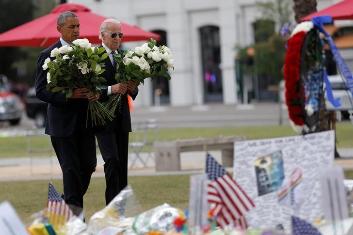 U.S. President Barack Obama (L) and Vice President Joe Biden place flowers at a makeshift memorial for shooting victims of the massacre at a gay nightclub in Orlando, Florida, U.S., June 16, 2016. REUTERS/Carlos Barria
